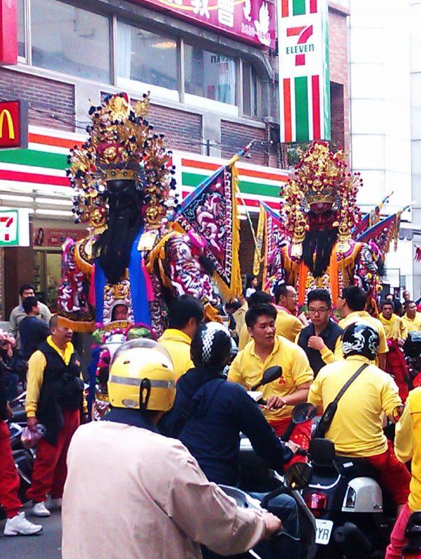 Une procession passe devant un 7eleven à Danshui